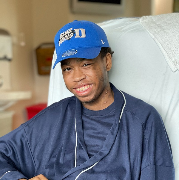 A heart transplant recipient smiles from his bed.